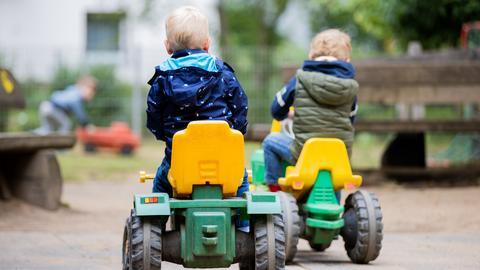 Zwei Kinder fahren auf Spielzeug-Traktoren