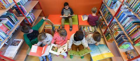 Kinder lesen in einer Schulbibliothek