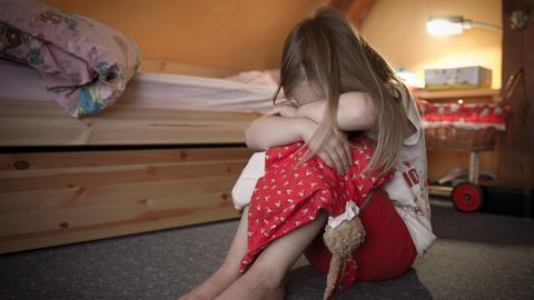 Ein kleines Mädchen sitzt weinend auf dem Fußboden in ihrem Zimmer.