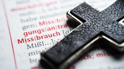 """Symbolbild: Ein Kreuz liegt auf einer offenen Buchseite, auf der das Wort """"Missbrauch"""" hervorgehoben ist."""