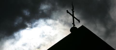 Eine Kirchturmspitze im Gegenlicht vor wolkenverhangenem Himmel.