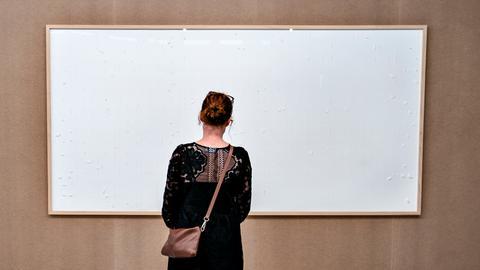Eine Frau steht vor einem leeren Bilderrahmen im Kunsten Museum in Aalborg.