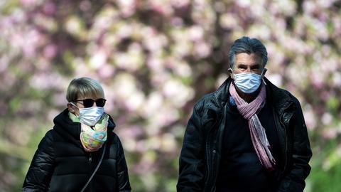 Ein älteres Paar geht spazieren und trägt Maske
