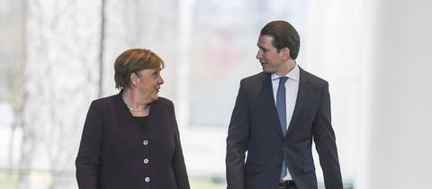 Angela Merkel und Sebastian Kurz spazieren nebeneinander her.