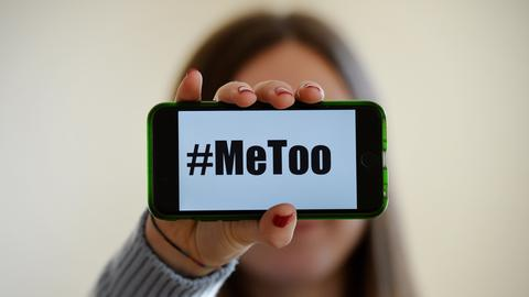 """Eine Frau hält ein Handy in die Kamera. Auf dem Display steht groß """"#MeToo""""."""