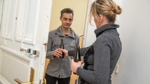 Eine Frau reicht ihrem Nachbarn im Hausflur ein Bier.