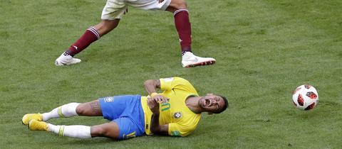 Neymar liegt am Boden und schreit laut auf.