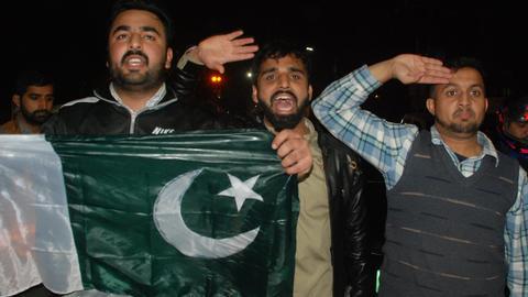 Demonstranten in Lahore halten eine pakistanische Flagge hoch und salutieren.