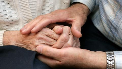 Sujetbild: Männerhände umfassen die Hände einer Seniorin.