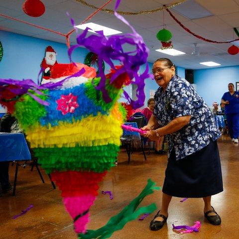 Eine Mexikanerin schlägt fröhlich auf eine Pinata ein.