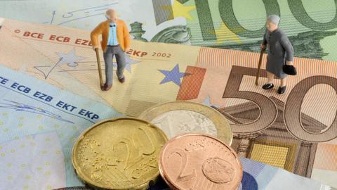 Zwei Rentner-Miniaturfiguren stehen auf einigen Euro-Scheinen