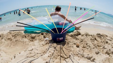 Ein Sangria-Eimer mit Strohhalmen am Strand von Arenal
