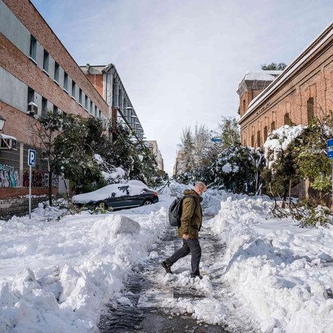 Ein Mann geht über eine schneebedeckte Straße in Spanien