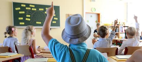 Blick von hinten in ein Klassenzimmer, in dem Schüler sitzen und sich melden.