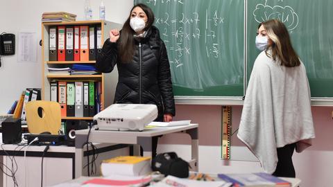 Eine Lehrerin und eine Schülerin stehen im Mathe-Unterricht mit Masken an der Tafel.
