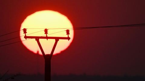 Die Sonne geht hinter einem Strommasten unter