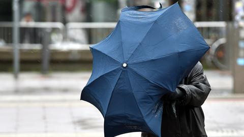 Eine Frau mit Regenschirm kämpft gegen den Sturm