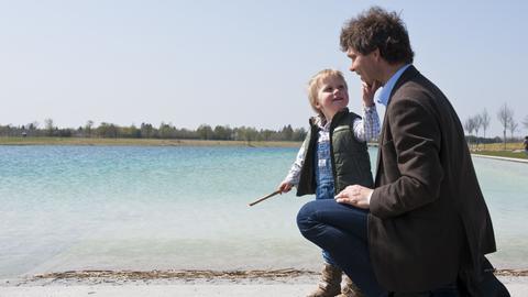 Vater und Sohn an einem See. Der Junior berührt den Vater am Kinn.