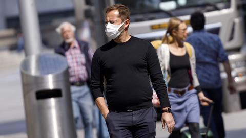 Sujetbild: Ein Mann mit Schutzmaske schlendert durch die Gegend, im Hintergrund sind Menschen ohne Masken zu sehen.