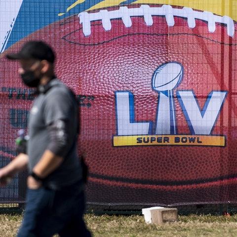 Ein Mann mit Maske läuft an einem Super-Bowl-Werbeplakat in Tampa (Florida) vorbei