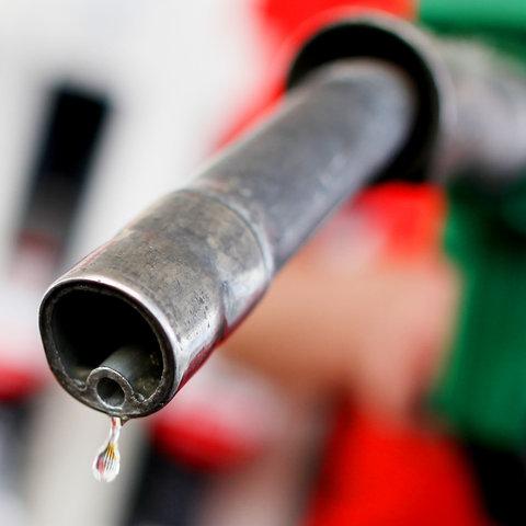 Ein Zapfhahn an einer Tankstelle, aus dem ein einzelner Tropfen läuft.