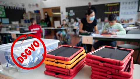 Klassenzimmer mit Kindern und Lehrerin im Hintergrund. Vorne liegen auf einem tisch Tablets in roten Hüllen. Auf dem Bild ist ein roter Stempel, der DSGVO in einem Kreis zeigt.