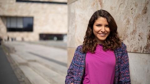 F-Wort Host, Dunja Sadaqi, lächelt selbstbewusst in die Kamera