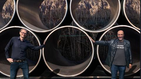 Omid Nouripour und Oliver Günther in einer Fotomontage vor Röhren der Nord Stream 2 Pipeline
