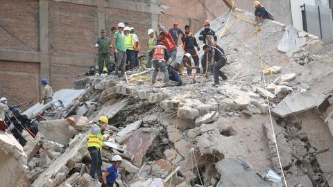 Helfer entfernen die Überreste eines eingestürzten Gebäudes.