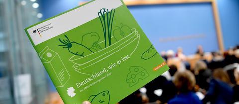 Hand hält Ernährungsreport mit grünem Cover hoch