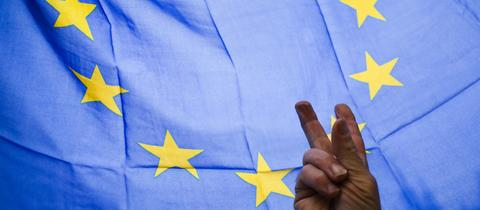 Eine Hand macht das Peace-Zeichen vor der EU-Flagge