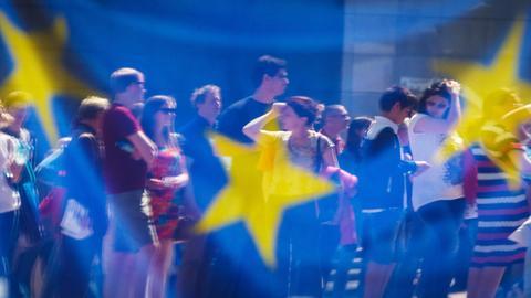 Eine Gruppe von Menschen vor einer EU-Flagge