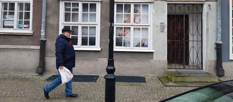 Spaziergänger vor einer Häuserfassade in Polen