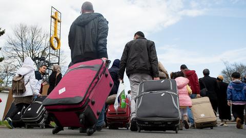 Syrische Flüchtlinge laufen mit ihrem Gepäck eine Straße entlang