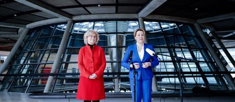 Christine Lambrecht in roter Jacke und Franziska Giffey in blauem Hosenanzug vor Mikros