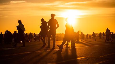 Menschen spazieren während des Sonnenuntergangs bei frühlingshaften Temperaturen auf dem Tempelhofer Feld.