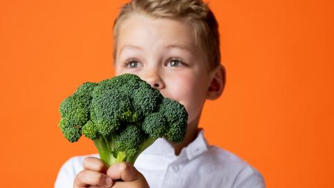 Junge hält einen Brokkoli