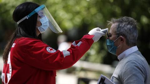 Eine Mitarbeiterin des Roten Kreuzes misst die Temperatur eines Mannes vor einem Gericht in Athen.