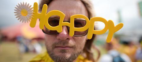 """Besucher des Glastonbury-Festivals in Großbritannien, der eine Brille mit dem Schriftzug """"Happy"""" trägt"""