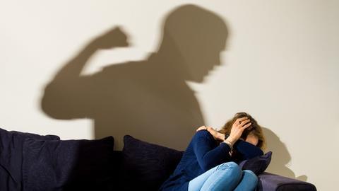 Schatten von Mann deutet an, Frau auf Sofa zu schlagen