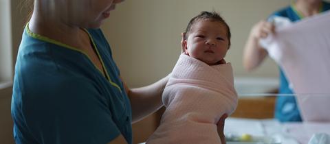 Eine Hebamme hält im Krankenhaus ein Baby im Arm