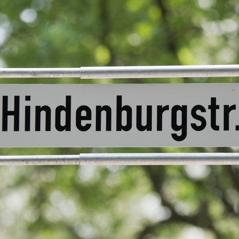 Straßenschild vor grünem Hintergrund auf dem Hindenburgstraße steht