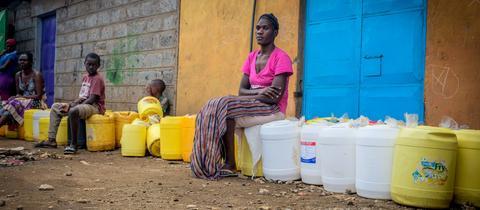 Kenia, Nairobi: Anwohner sitzen auf Kanistern in einer Reihe mit Abstand voneinander, um Wasser zu holen.