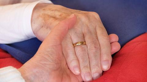 Die Hand eines Demenzkranken wird gehalten.