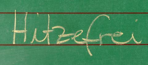 """Das Wort """"Hitzefrei"""" steht an einer Schultafel."""