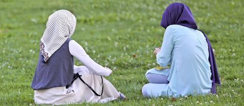 Zwei junge Muslima mit Kopftuch sitzen auf einer Wiese.