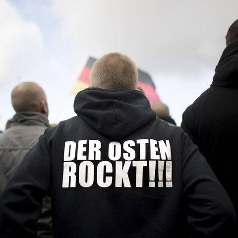 """Ein Mann trägt eine Jacke auf der """"Der Osten rockt"""" steht"""