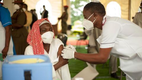Eine Frau in weißem Kittel und mit Mundschutz spritzt eine Frau sitzend mit Kopftuch