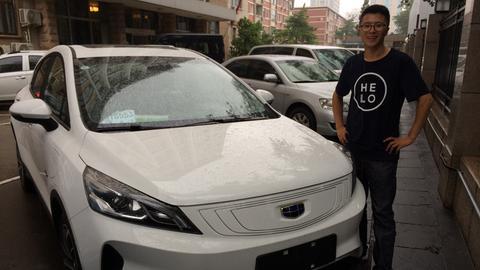 Li Qi steht stolz vor seinem neuen Elektro-Auto