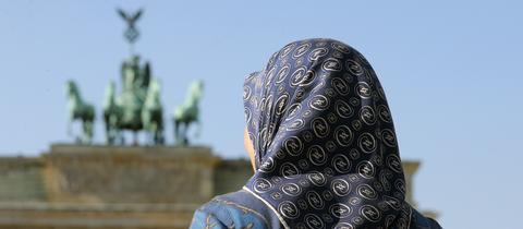 Eine Frau im Kopftuch steht vor dem Brandenburger Tor in Berlin